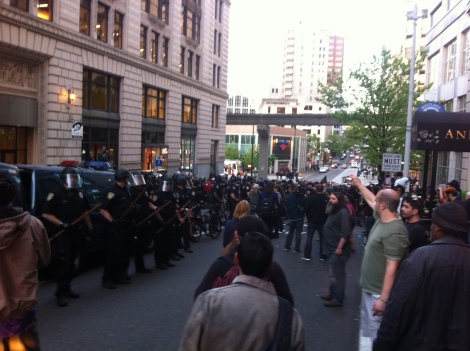 Police lined up while flash bang grenades and chemical sprays go off down the street. Photograph by Alexander M. Koch.
