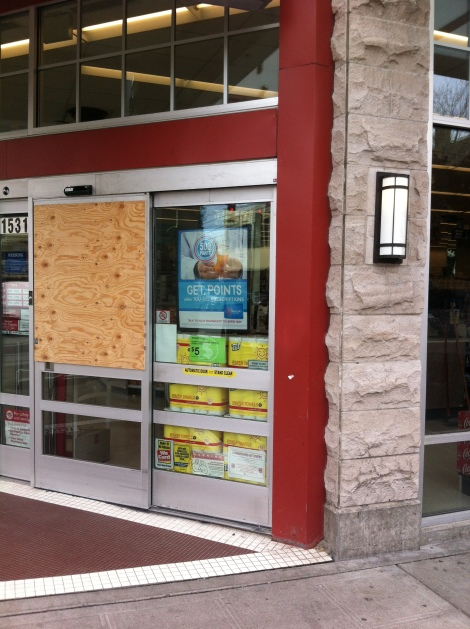 Day-after photo of Walgreens broken, boarded up window. Photograph by Alexander M. Koch.