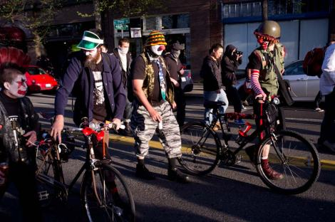 Protesters dressed as clowns on bicycles lead a May Day march through Seattle, WA. Photograph by Dean Wenick.