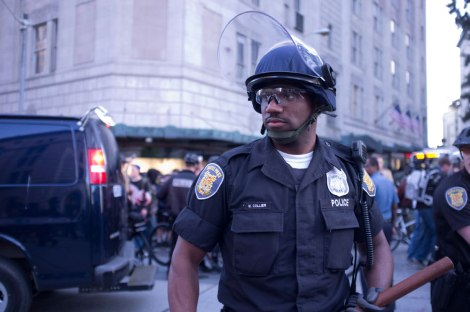 Officer Collier of the Seattle Police Department prepares to clash with protesters. Photograph by Dean Wenick.