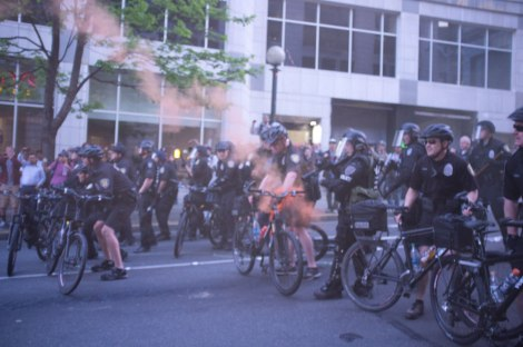 A smoking projectile hits a policeman in the stomach during MayDay protests in Seattle, WA. 1 May, 2013. The anti-capitalist march did not have a permit and resulted in confrontations between protesters and police. Photograph by Dean Wenick.